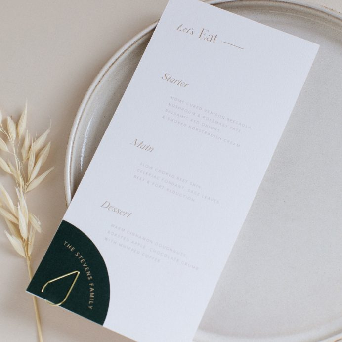 Refined gold wedding menu with digitally printed gold. Quarter circle shape guest name tag attached with a clip.